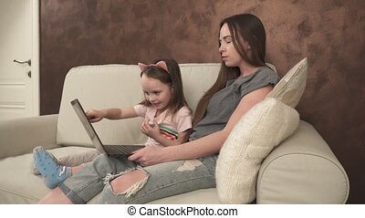 Little girl shows something to her mother on the laptop