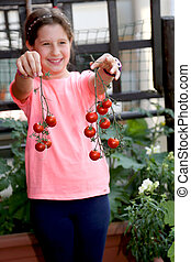 little girl shows the harvest of tomatoes smiling