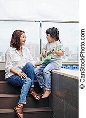 Little girl singing for mother