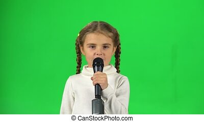 Little girl singing into microphone on green screen at studio