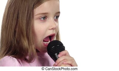 Little girl sings the song into the microphone. White background. Close up. Slow motion