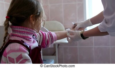 Little girl sit at surgery, doctor comes and makes injection