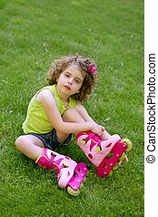 Little girl sit on the grass with roller skates