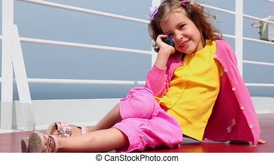 Little girl sits and talk by cell phone on deck near fence