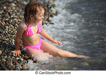 little girl sits ashore in waves