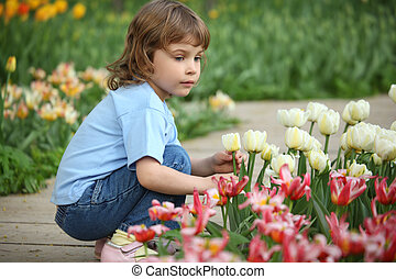 little girl sits at bed with tulips