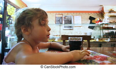 Little girl sits at table and drink from glasses carbonated water