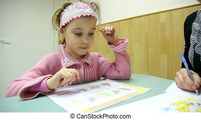 Little girl sits at table with book and utters words, ...