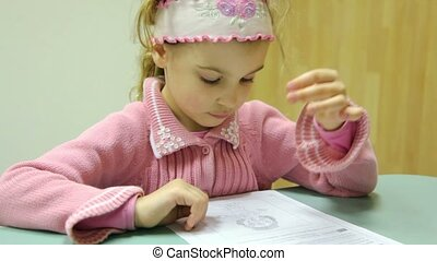 Little girl sits at table with piece of paper and reads test