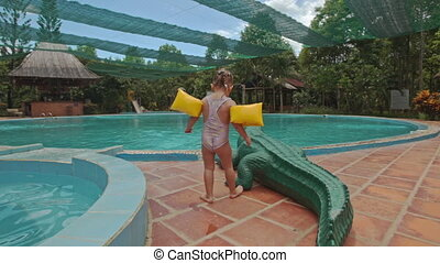 Little Girl Sits down on Toy Crocodile by Pool at Hotel