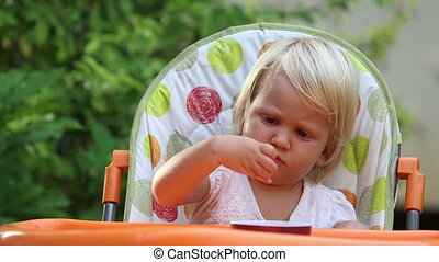 little girl sits in  chair and eats grapes