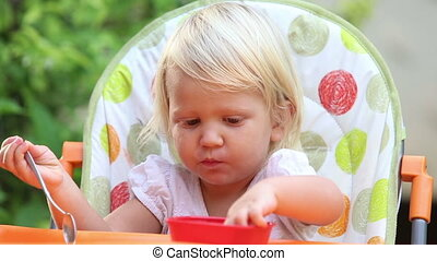 little girl sits in  chair and eats mango with spoon