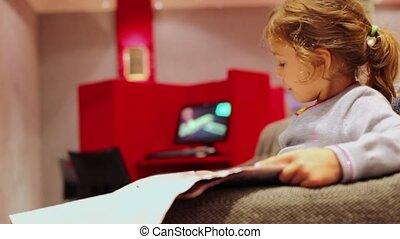 Little girl sits in chair and reads aloud newspaper at room