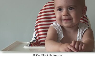 little girl sits in child's chair