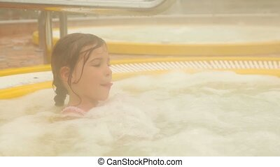 Little girl sits in pool and vapor covers all around -...