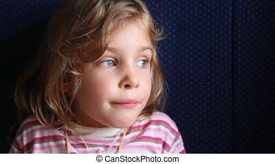 Little girl sits in train.