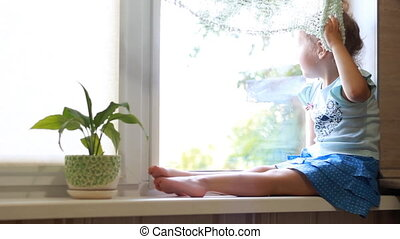Little girl sits on a window sill and looks out the window. The concept of expectation.