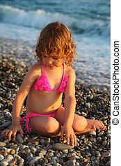 little girl sits on beach