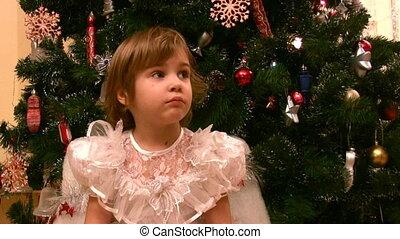 little girl sits on chair near christmas tree