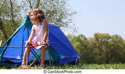 Little girl sits on chair near small tent