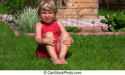 little girl sits on green grass in outlet