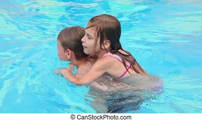 Little girl sits on her brother back and they swim in pool