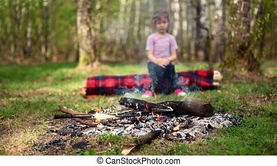 Little girl sits on log and watch at bonfire burn