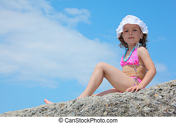 little girl sits on rock against sky