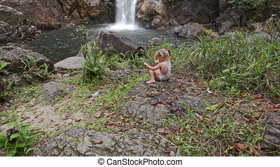 Little Girl Sits on Stone against High Waterfall Cascade