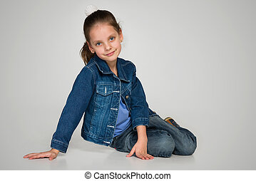 Little girl sits on the gray background