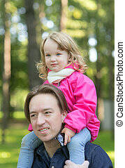 little girl sits on the shoulders