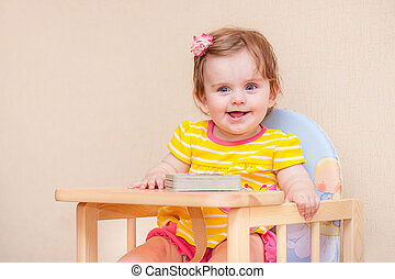 little girl sitting at a table in front of book.