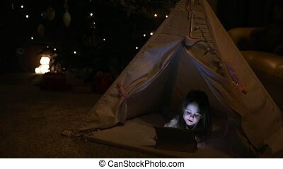 Little girl sitting at home in a tent against the background of a Christmas tree playing games on an electronic tablet. Blurs and looks at the screen.