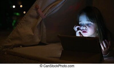 Little girl sitting at home in tent on background of Christmas tree talking on video communication with dad via electronic tablet lying on floor of house.