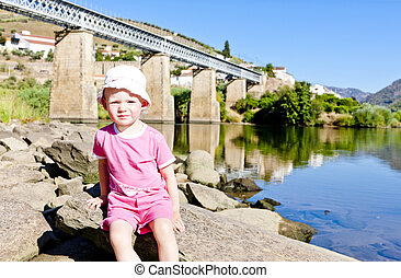 little girl sitting at railway viaduct in Douro Valley, Portugal