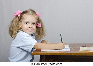 Little girl sitting at the table an