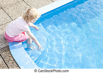 little girl sitting by swimming pool