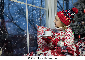 little girl sitting by the window and christmas tree