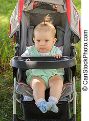 little girl sitting in a baby carriage