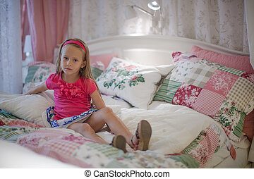 Little girl sitting in a big colorful bed