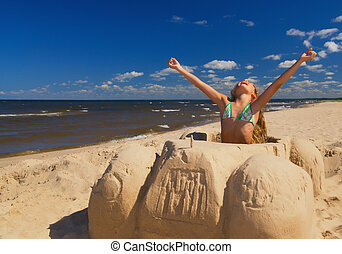 Little girl sitting in a car made of sand