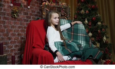 Little girl sitting in a chair at the Christmas tree