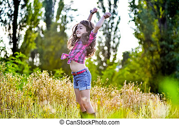 little girl sitting in a field wearing a cowboy hat