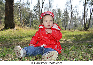 Little girl sitting in a forest.