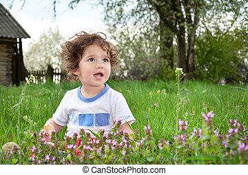 Little girl sitting in a meadow.