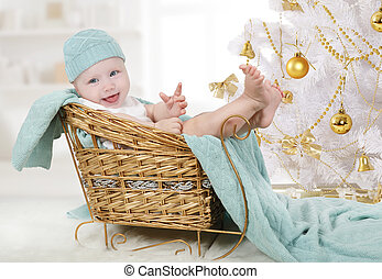 Little girl sitting in a sleigh under a Christmas tree