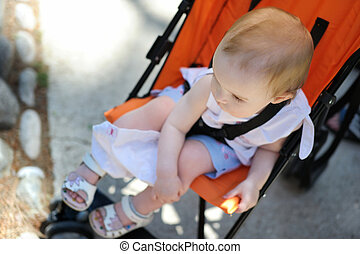 Little girl sitting in a stroller