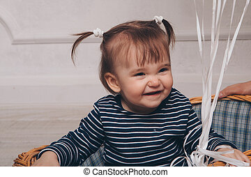 little girl sitting in basket on white background