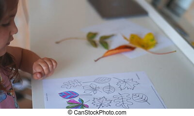 4k video of a little brunette girl in a pink dress sitting in front of a mirror and a white desk with coloring leaves images on a paper sheet alongside some real leaves