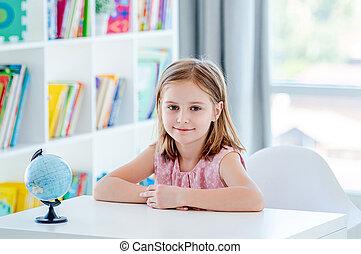 Little girl sitting in light classroom